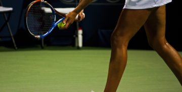 Woman holding a tennis racket and about to serve