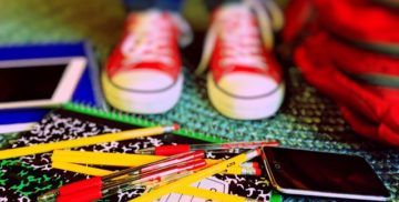 Kid's shoes, pencils, notebook, phone